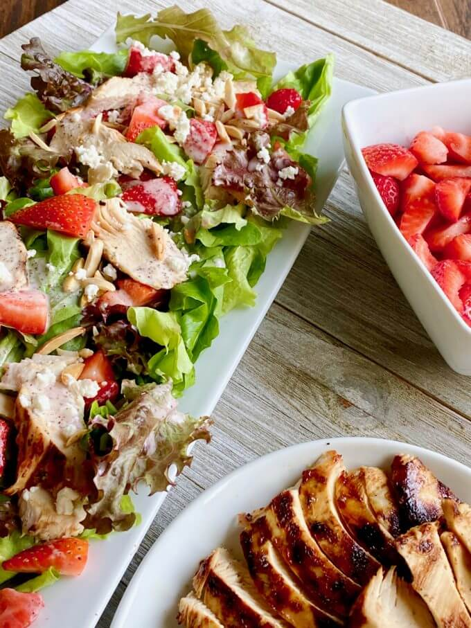 Chicken Strawberry Salad with a bowl of strawberries and a plate of chicken