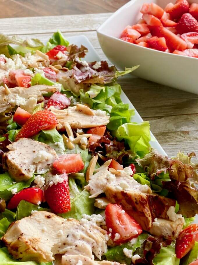Chicken poppyseed salad with a bowl of strawberries in the background