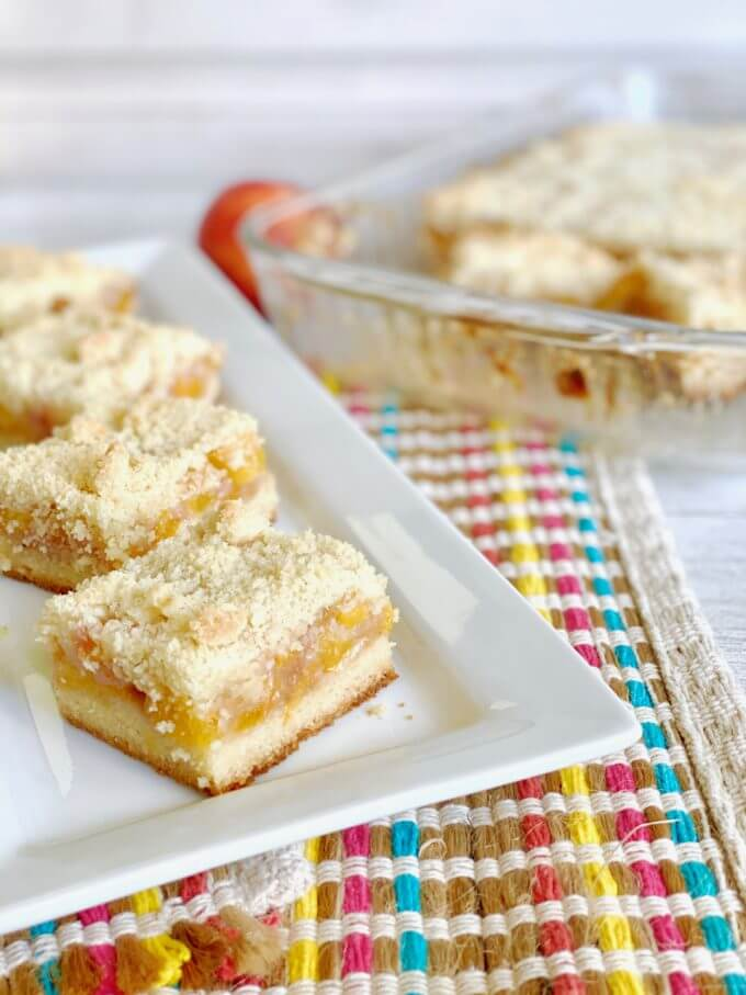 four peach crumb bars on a plate
